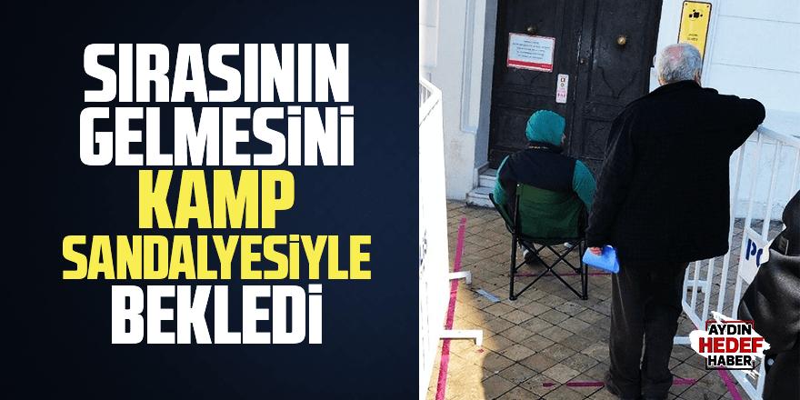 Kamp sandalyesiyle sırasını bekledi
